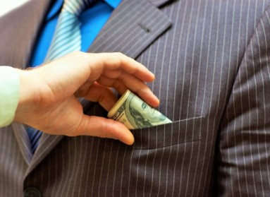 Man putting money into businessman side pocket
